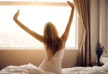 Frau wacht auf im Bett