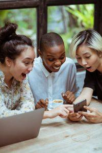 Youtube Seo: Drei Frauen schauen auf ein Handy