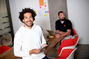 Duales Studium BWL: Mann mit Tablet im Meetingraum