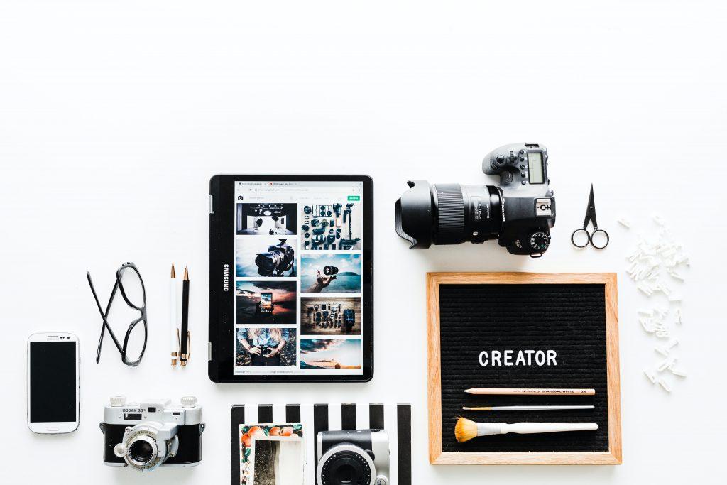 Flatlay von ipad, Fotokamera, Smartphone und Brille in der Influencer Ausbildung
